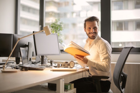 man-smilling-sitting-desk